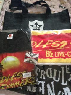 上:ショッピングバッグ 右:マフラ~タオル 下:フェイスタオル 左:ツア~Tシャツ 中央:チャリティブレス